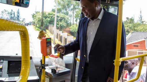 Male Black Commuter entering bus using Tap & Go payment system
